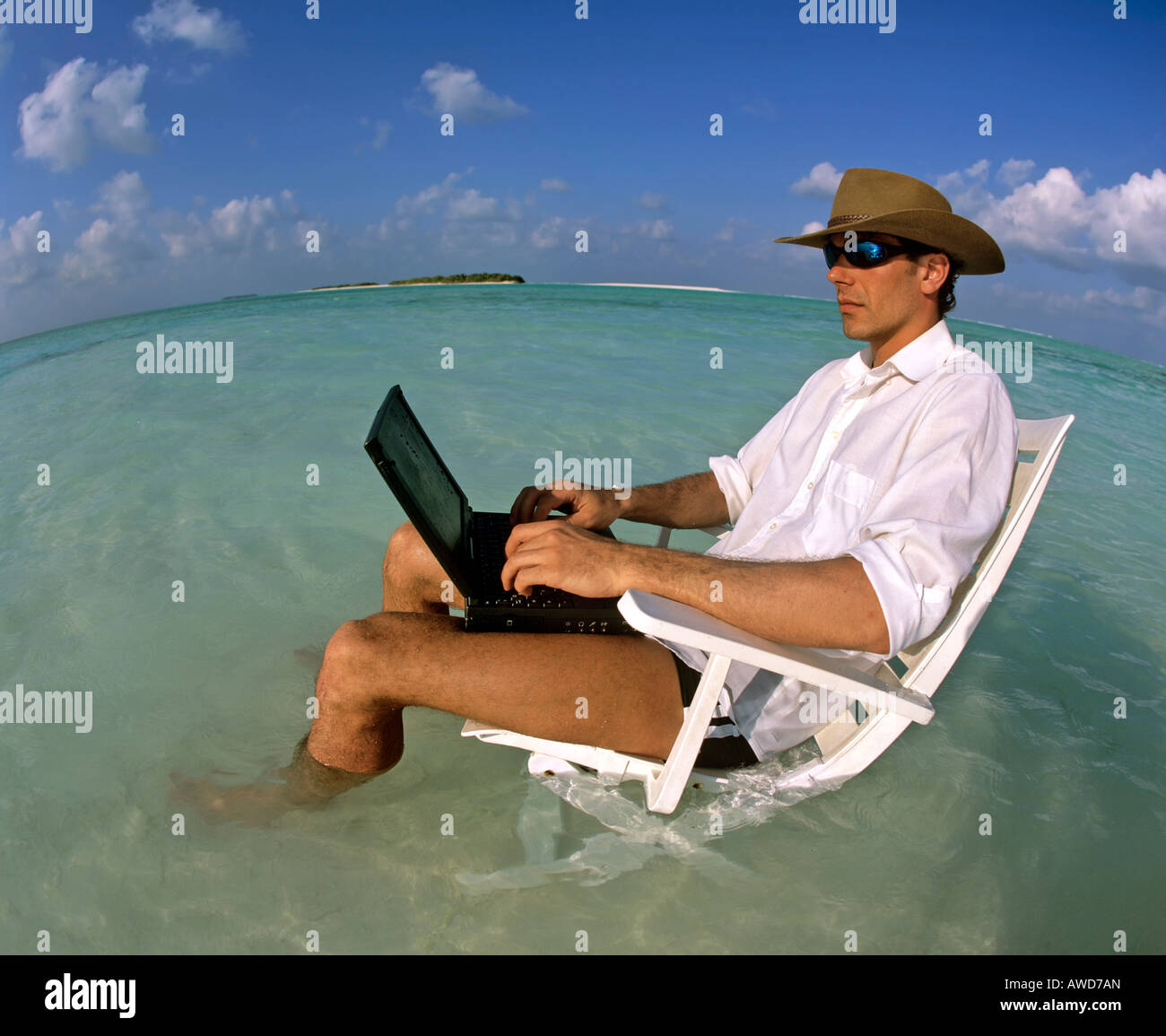 Young man with laptop sitting on deck chair work and relaxation Stock Royalty Free Image
