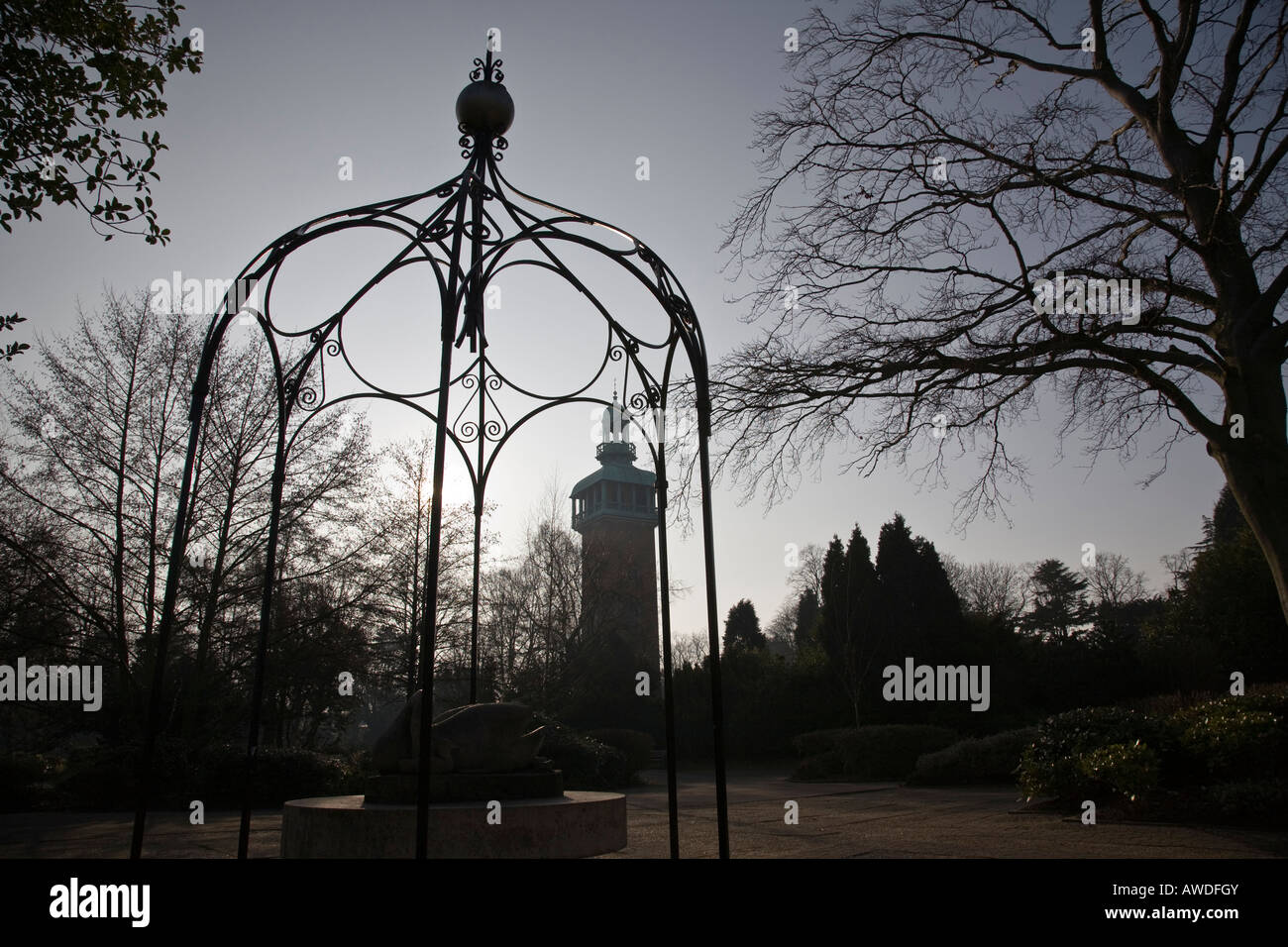 A Wrought Iron Pergola Covers Statue With The Carillon Bell Tower Silohuetted In Background Loughborough England