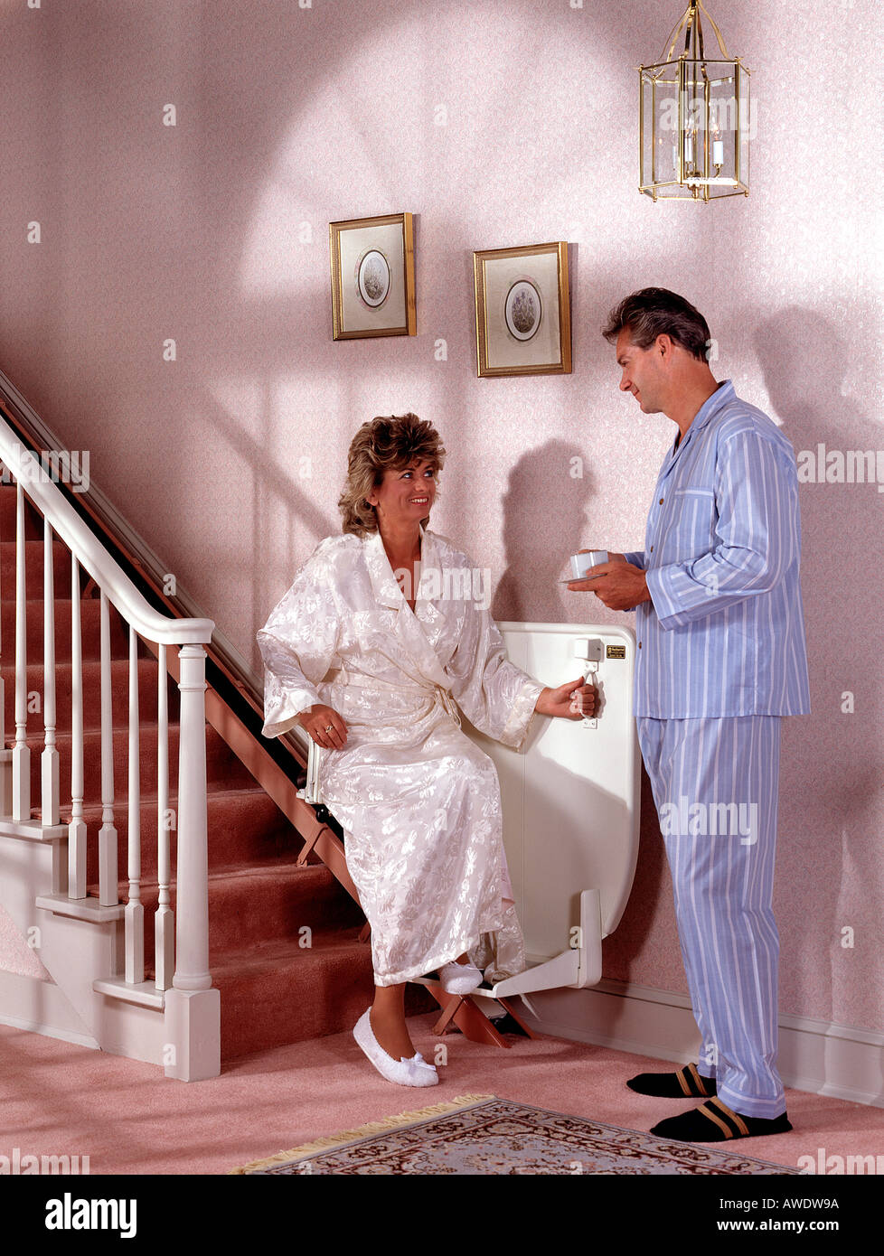 home chair elevator. stock photo - couple man wife male female using in home chair lift elevator handicap