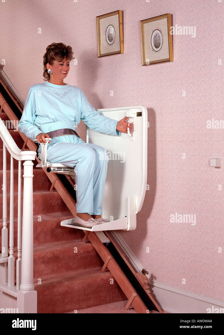 home chair elevator. stock photo - middle age aged woman female using stair chair lift elevator in home handicap copy space t