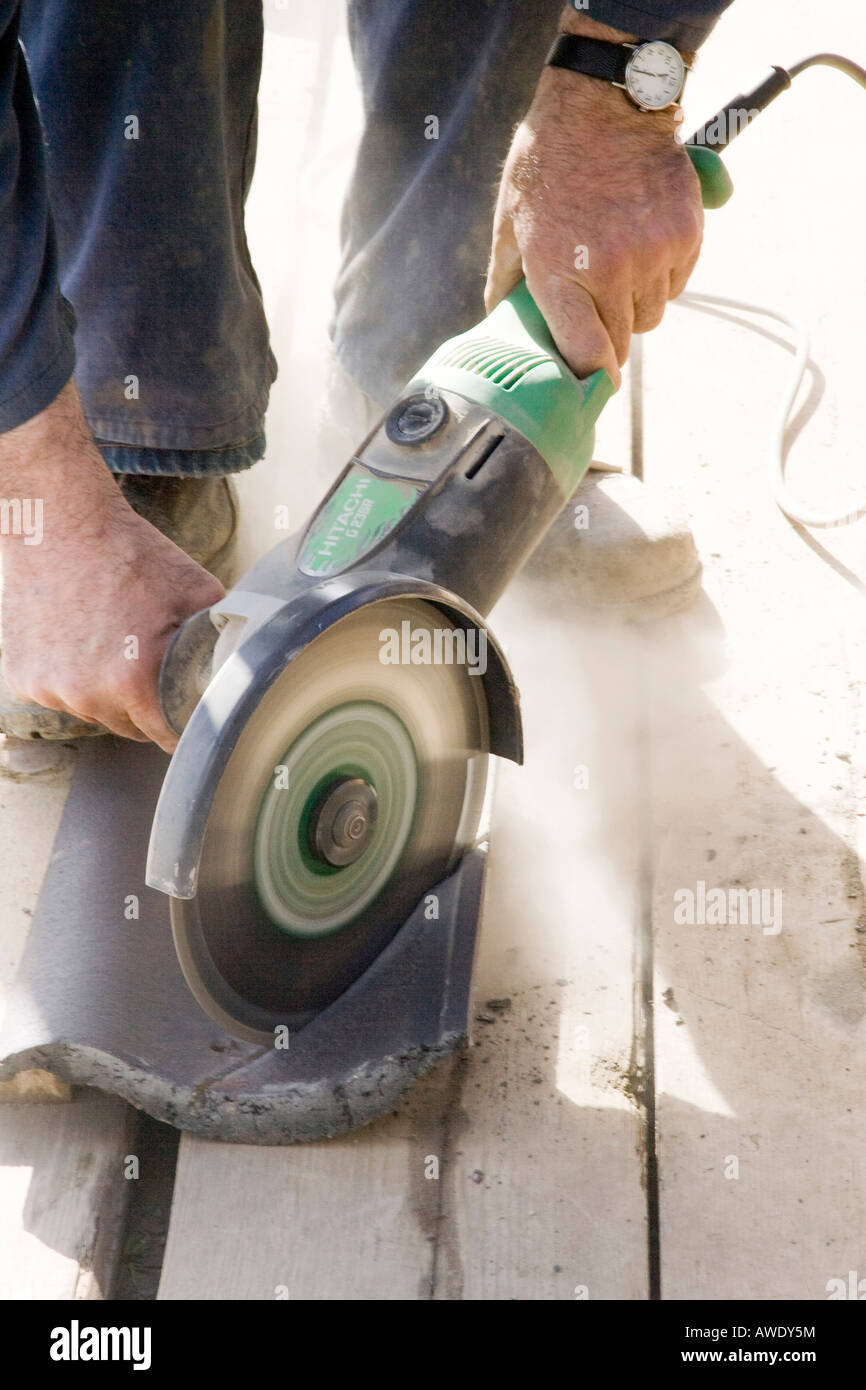 Worker cutting a tile using an angle grinder at construction site builder cutting roof tiles with an angle grinder stock photo dailygadgetfo Image collections