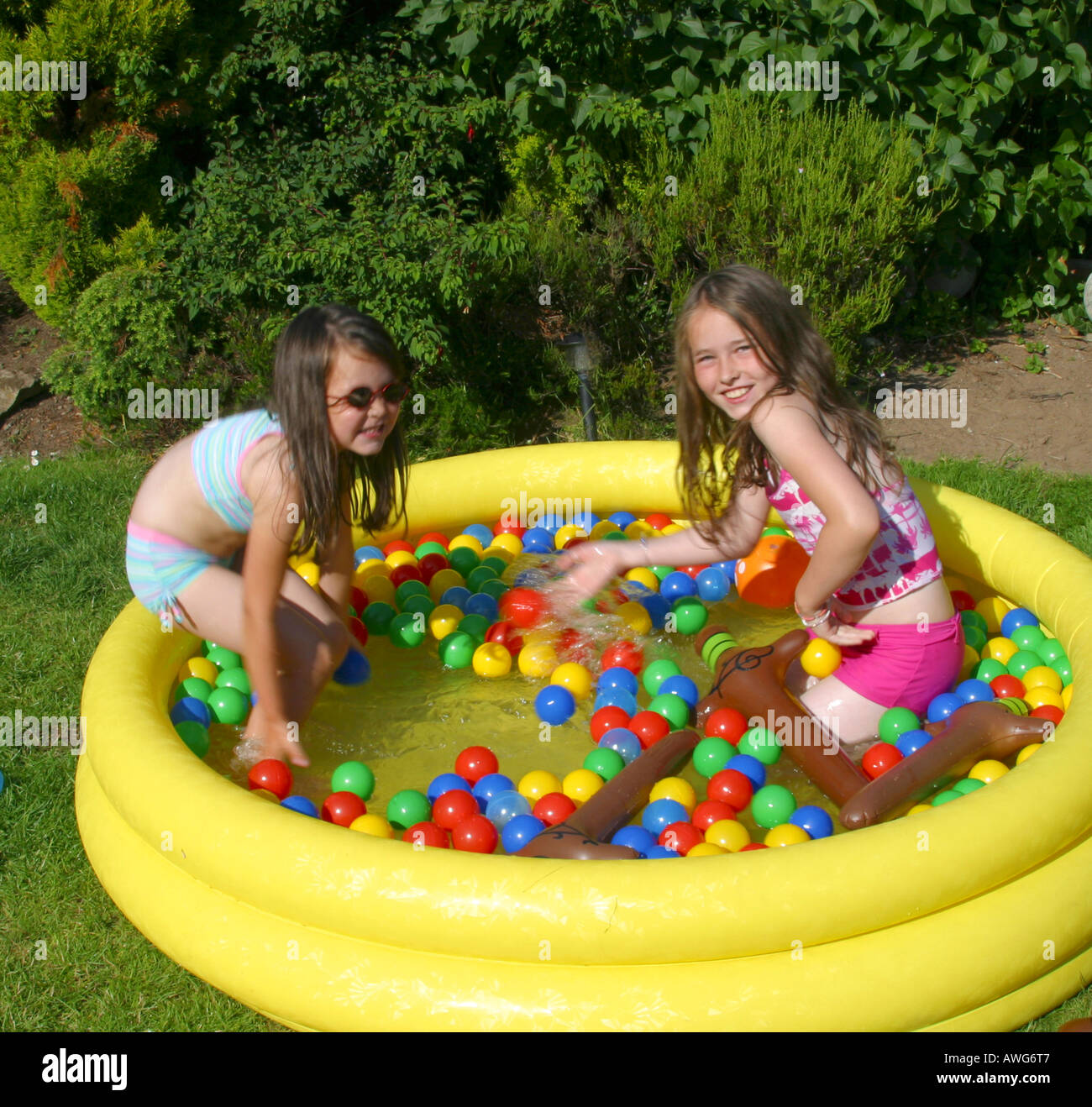 Two young girls playing in paddling pool in garden stock for Garden paddling pools