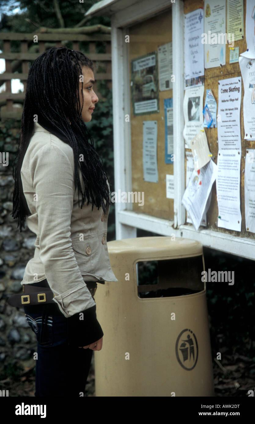 mixed race teenage girl looking at job vacancy adverts on notice stock photo mixed race teenage girl looking at job vacancy adverts on notice board