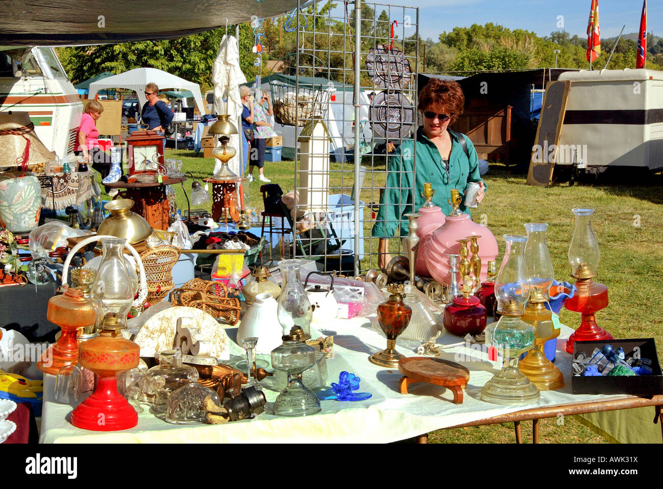 Stock Photo   Woman Examines Items On Table At Flea Market Swap Meet Sale  Including Number Of Very Old Oil Lamps Economy