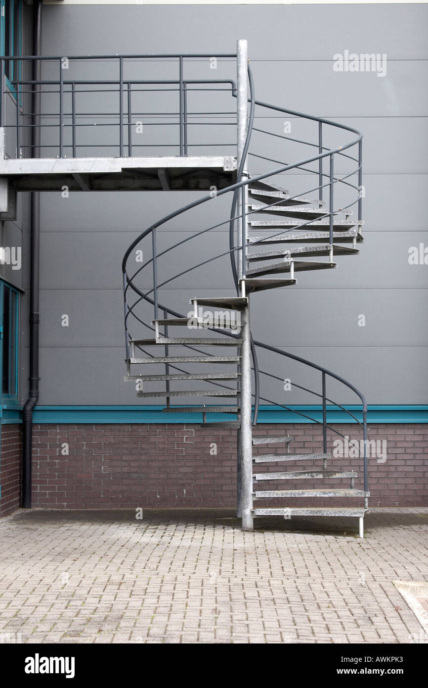 Galvanised Steel Metal Fire Escape Spiral Staircase Outside Office And  Warehouse Building In Western England UK