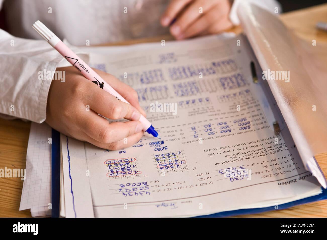 Young schoolgirl doing homework in nursery, mathematics exercises ...