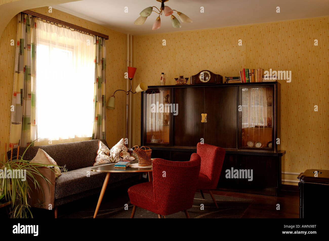 1950s living room with cabinet sofa armchair lamp and table