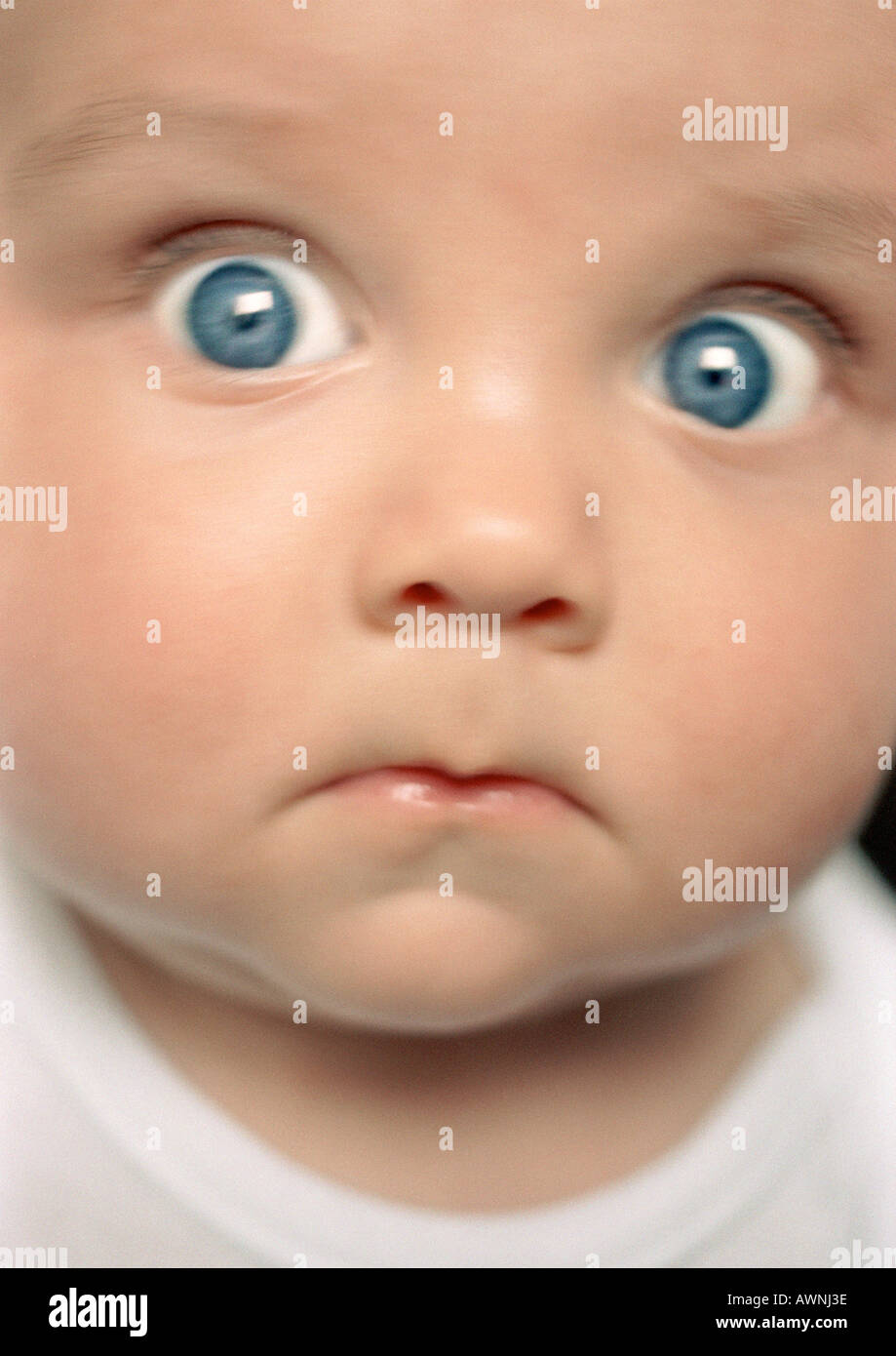 baby looking at camera with eyes wide open close up stock