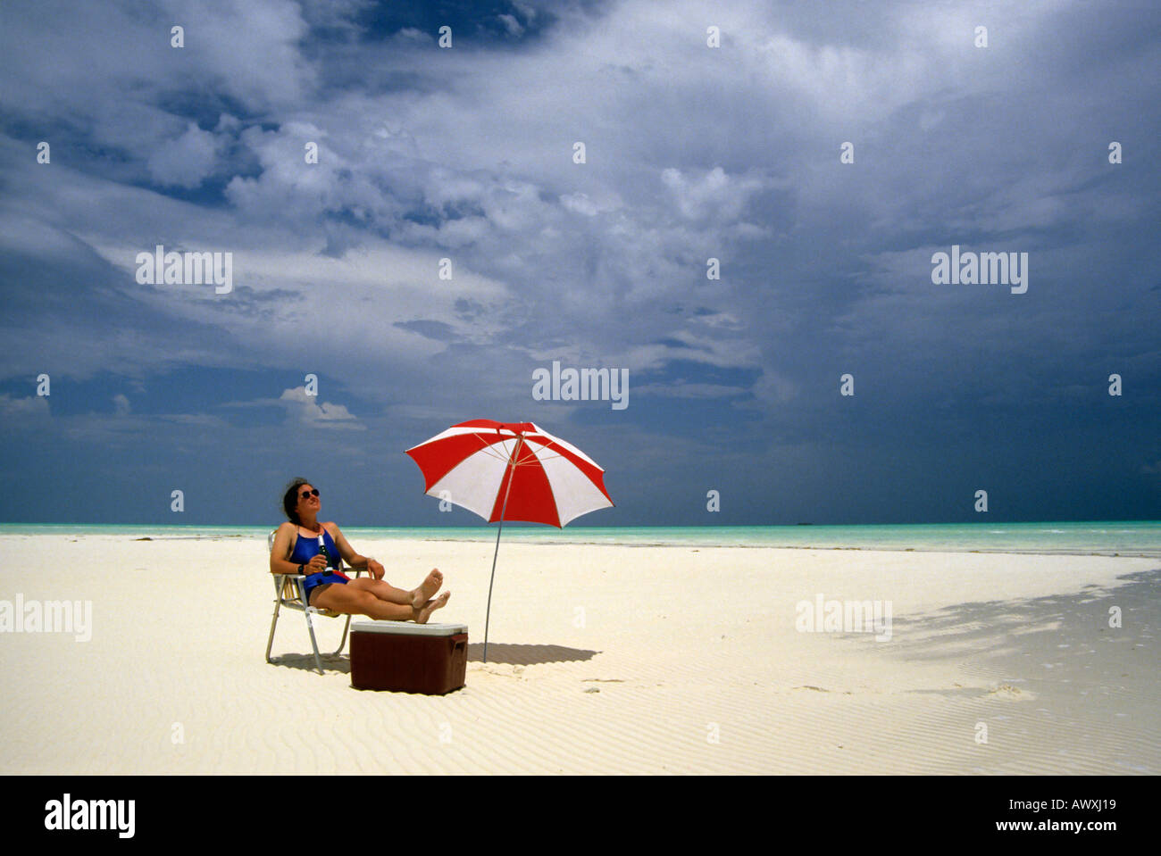 Female On Beach With Drink Cooler And Umbrella Andros Island Bahamas