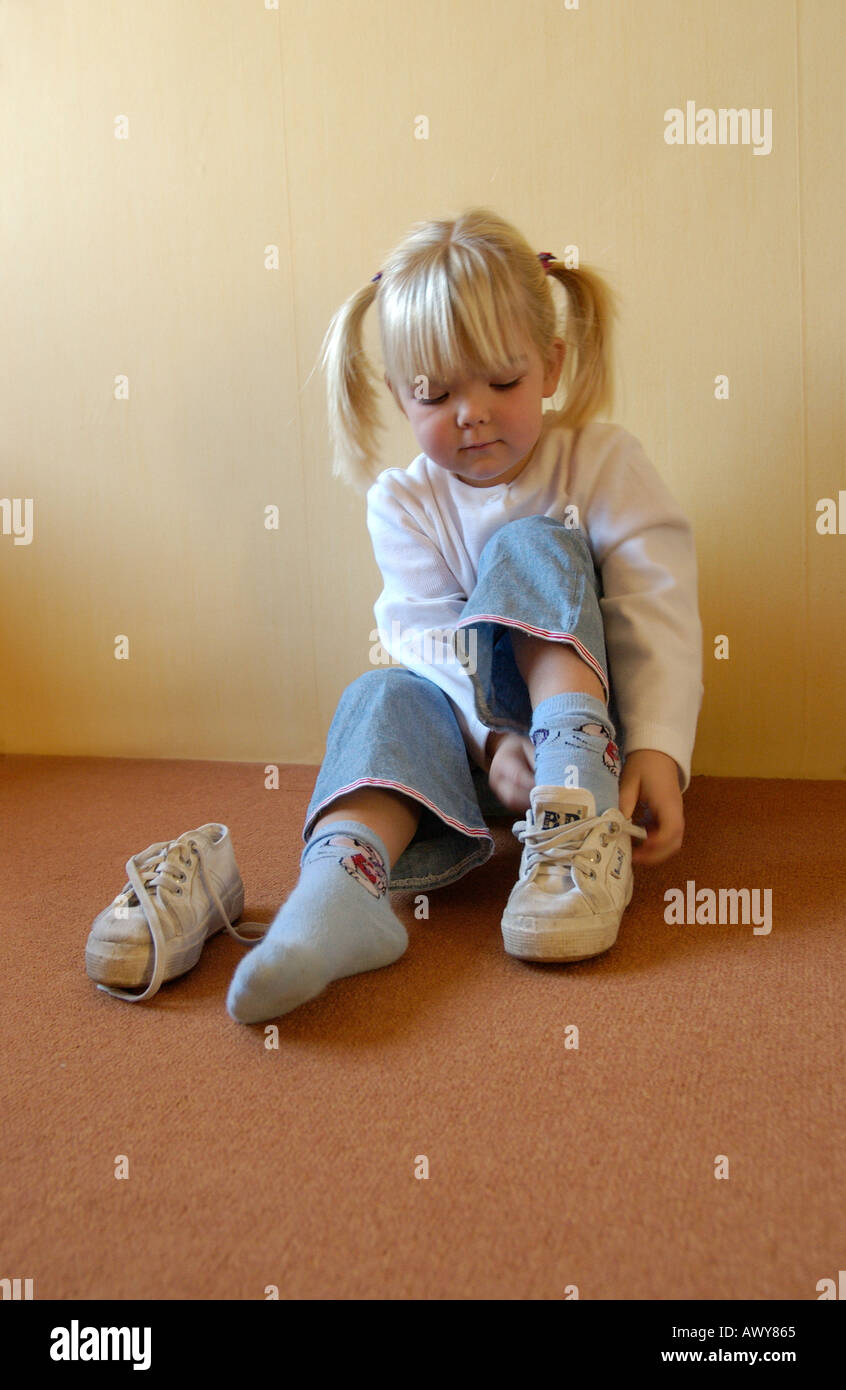 Little girl putting on her shoes Stock Photo, Royalty Free ...