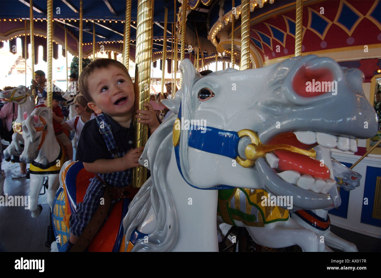 One year old toddler on a merry-go-round, riding a horse, at ...