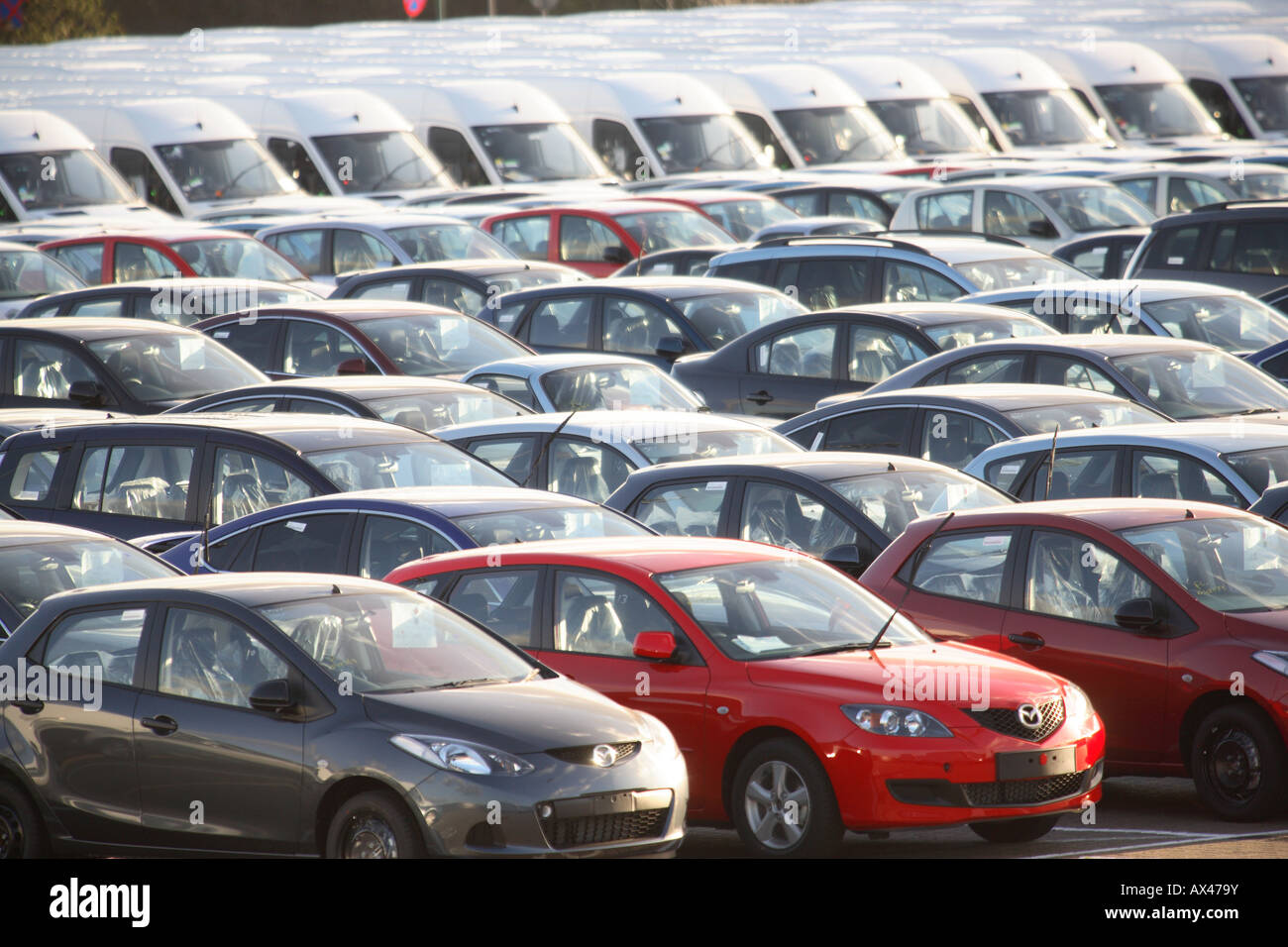 rows of brand new cars and vans in a car lot awaiting distribution