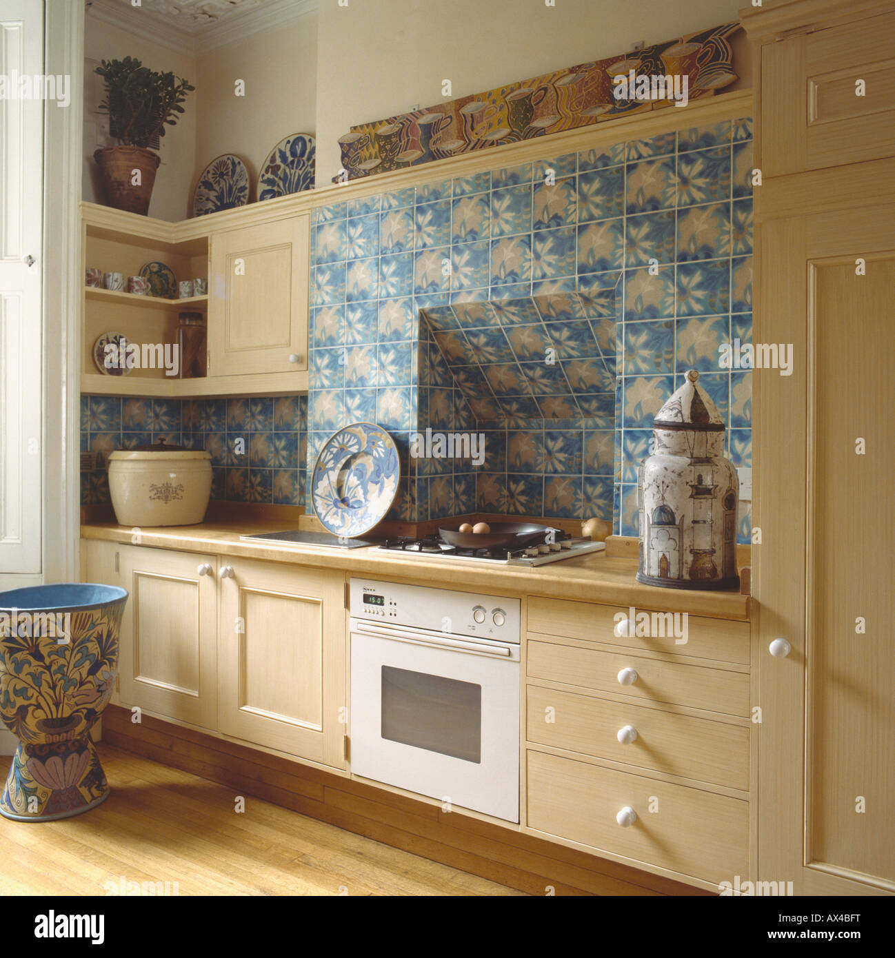 Blue Floral Tiles Above White Built In Oven In Neutral Eighties Kitchen With Large Ceramic Ornamental Pot
