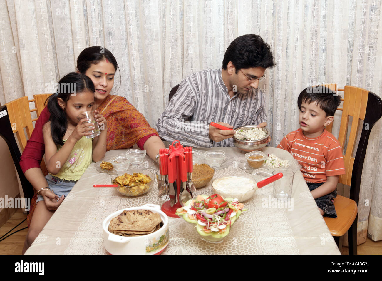 Family Eating Food At A Dining Table Stock Photo Royalty