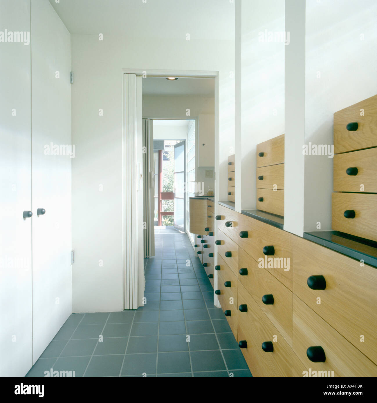 Grey floor tiles and beech storage units on long corridor with ...