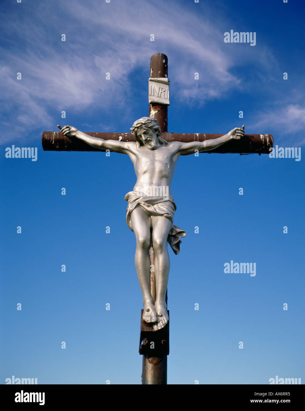silver statue of jesus christ on dark wooden cross with red