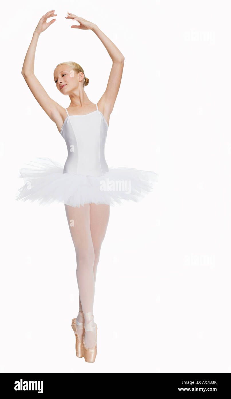 Young ballerina (14-15) standing on pointe in toe shoes ...