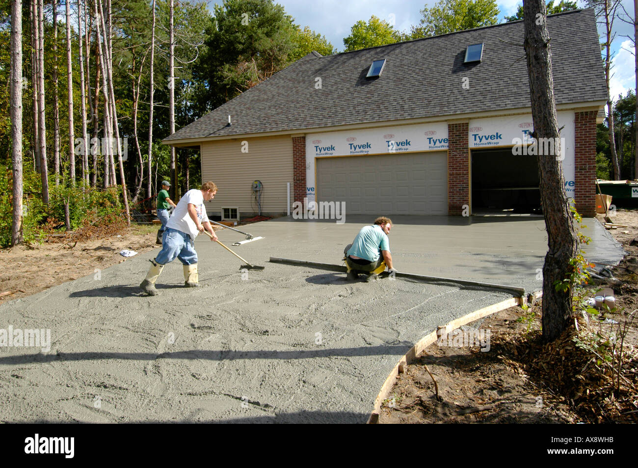 Cement mason workers pour and finish a concrete driveway for How to pour a concrete driveway