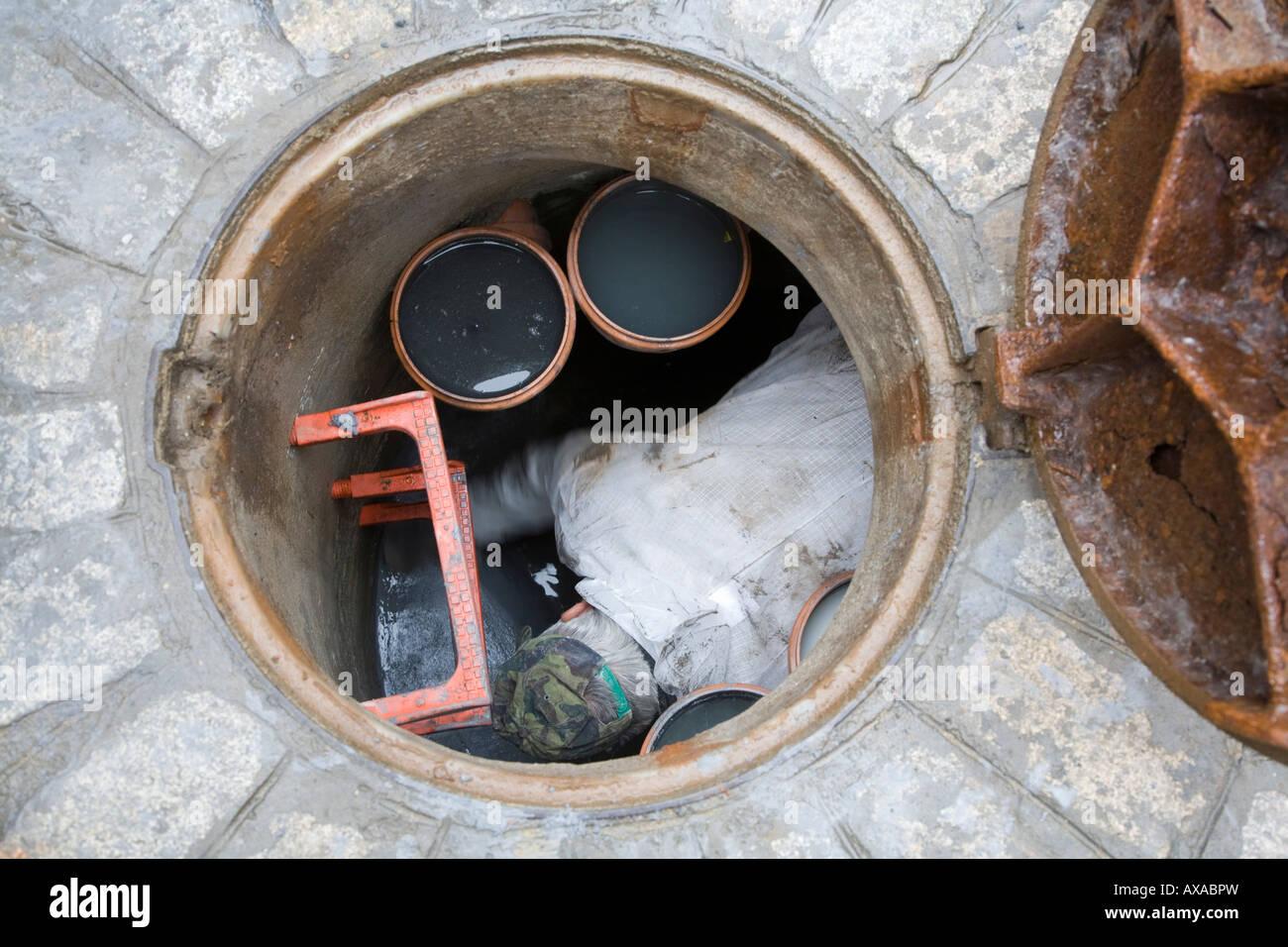 Sewer worker inside a manhole seville spain stock photo