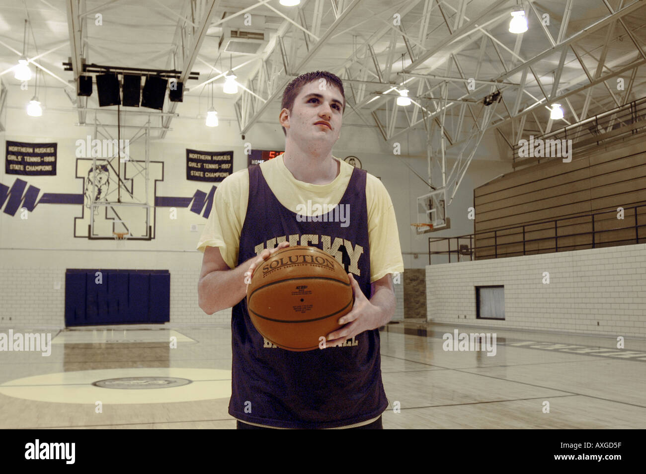 high basketball player stands at the free throw line under