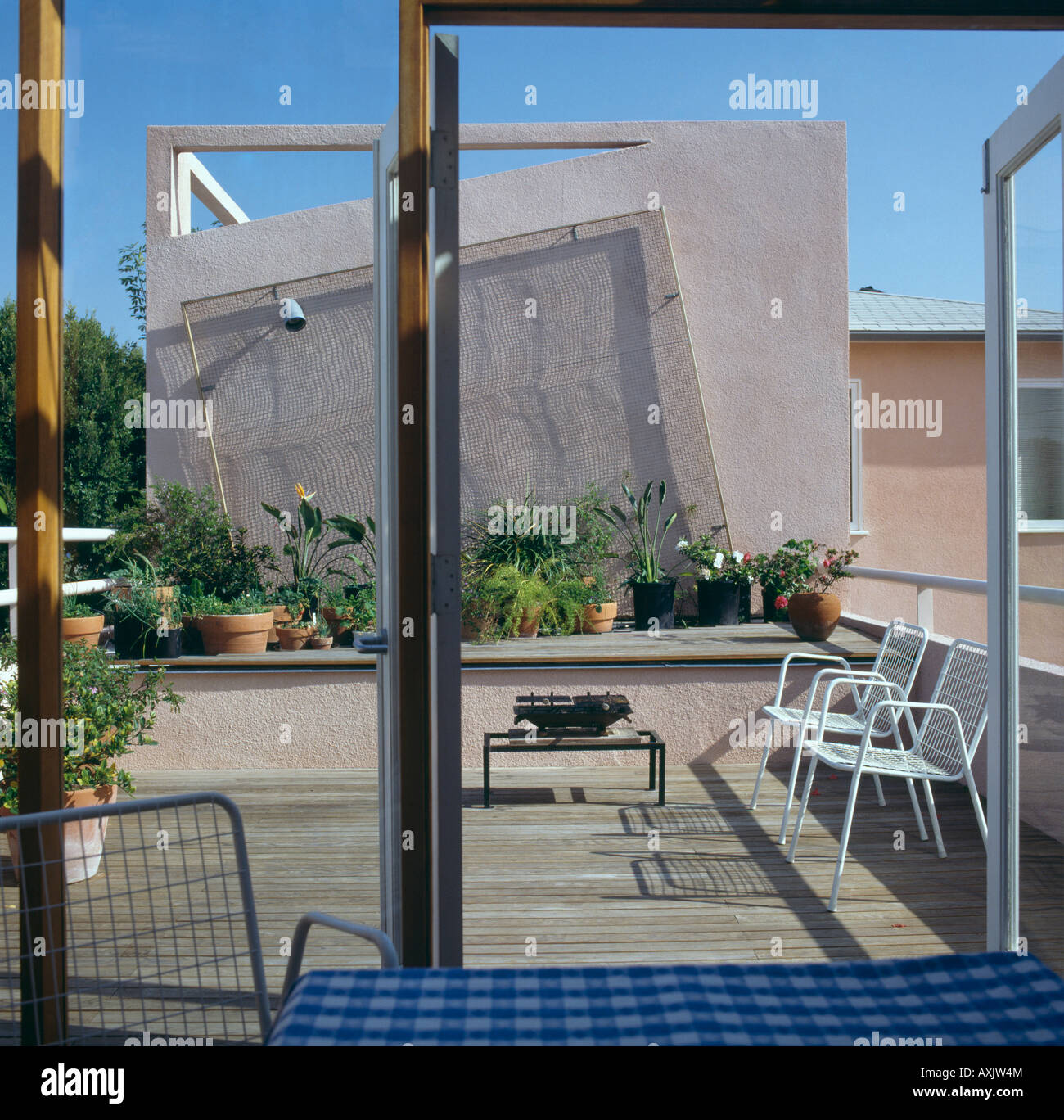 View through glass doors of dining room to decked city roof terrace with barbeque and white chairs and plants in pots & View through glass doors of dining room to decked city roof terrace ...