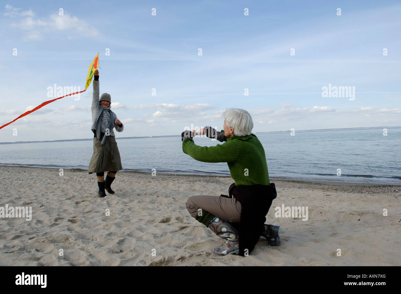 two mature women flying a kite at baltic sea beach stock photo