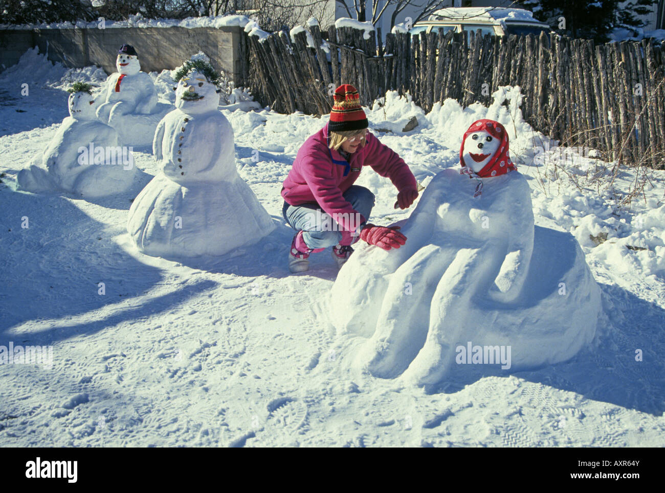 usa new mexico santa fe a woman makes a snowman and snowwoman after a stock photo royalty free. Black Bedroom Furniture Sets. Home Design Ideas