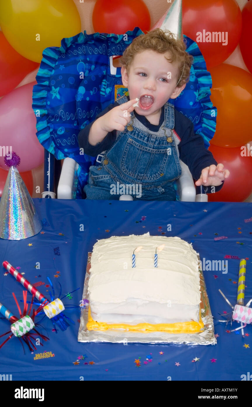 Two year old boy celebrating his birthday with birthday cake Stock