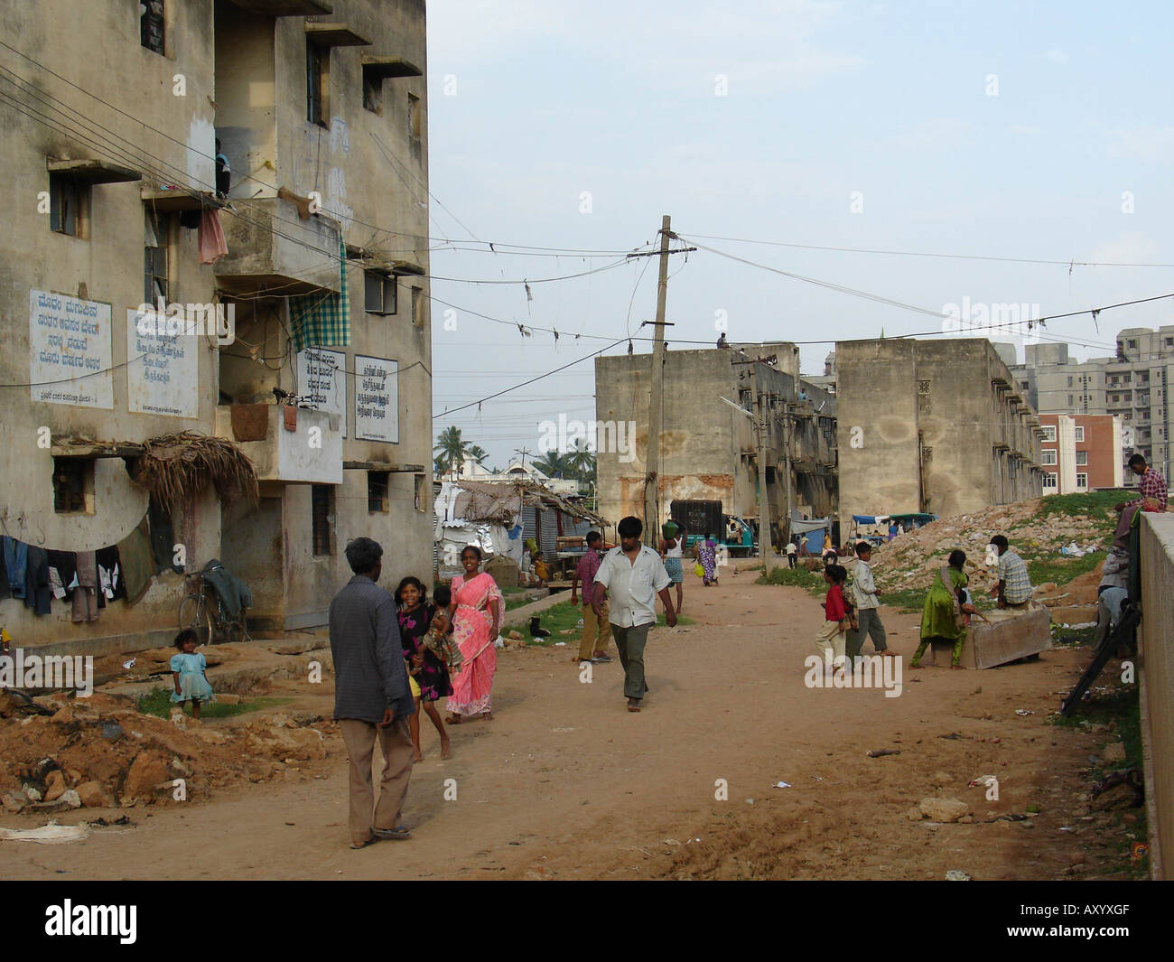 Houses in bad shape with indian characters near to a big for Big house images in india