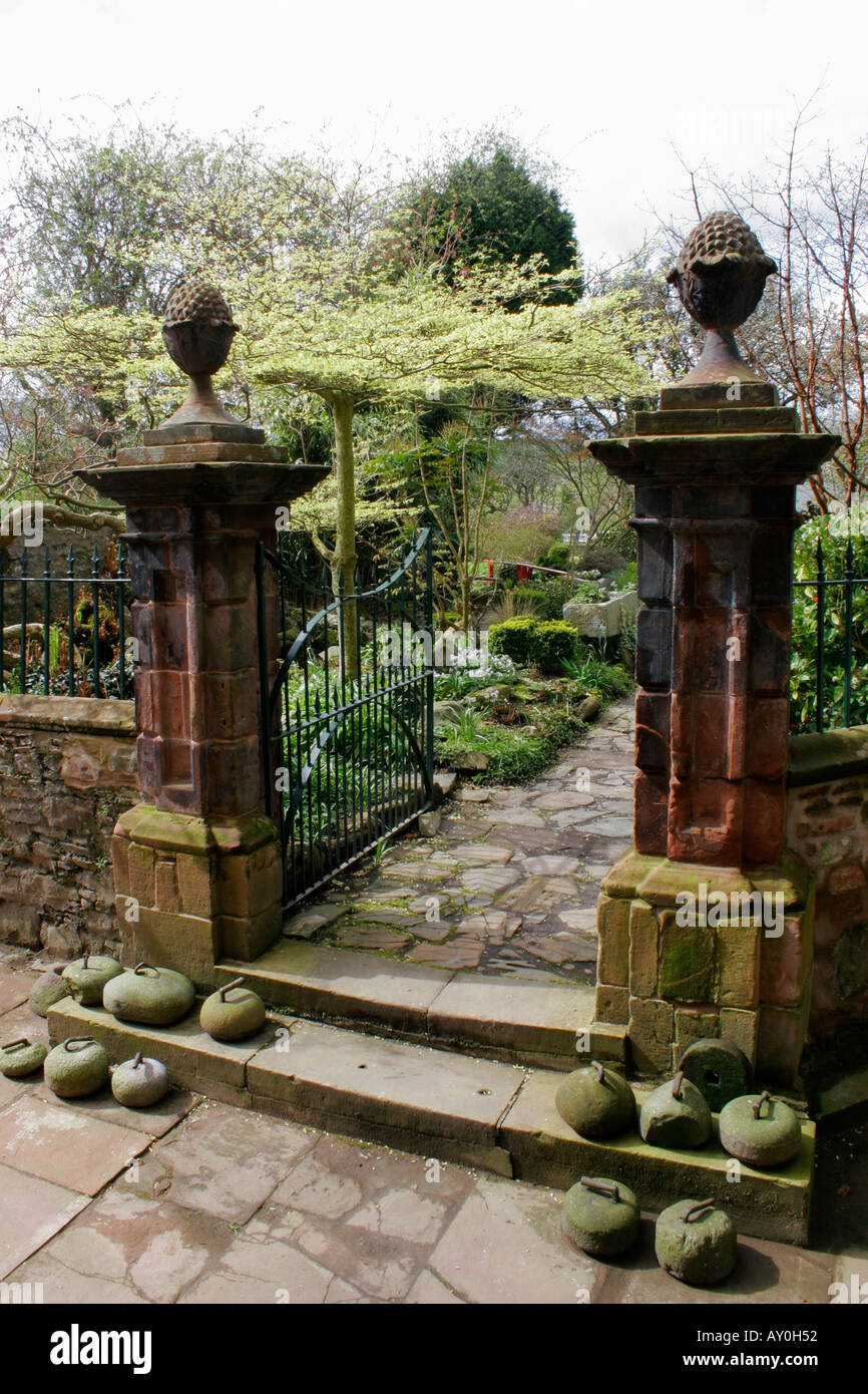 Old Sandstone Gate Pillars With Pineapple Finials In Garden At