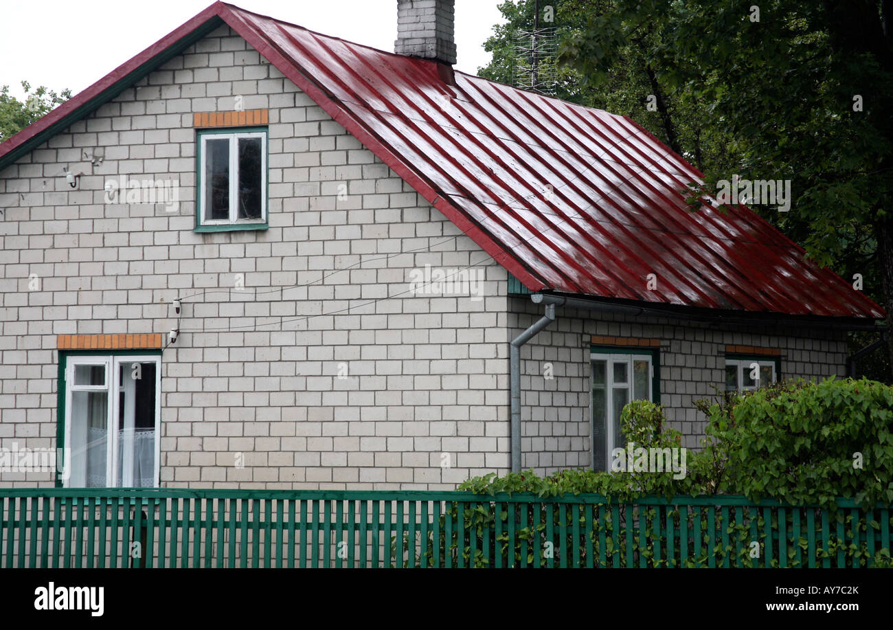 Two story house with bright red metal roof green trim on for Roof height of 2 story house