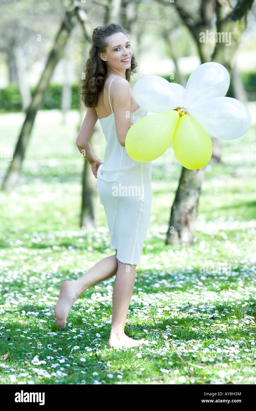 Young woman walking barefoot in meadow, holding balloons ...