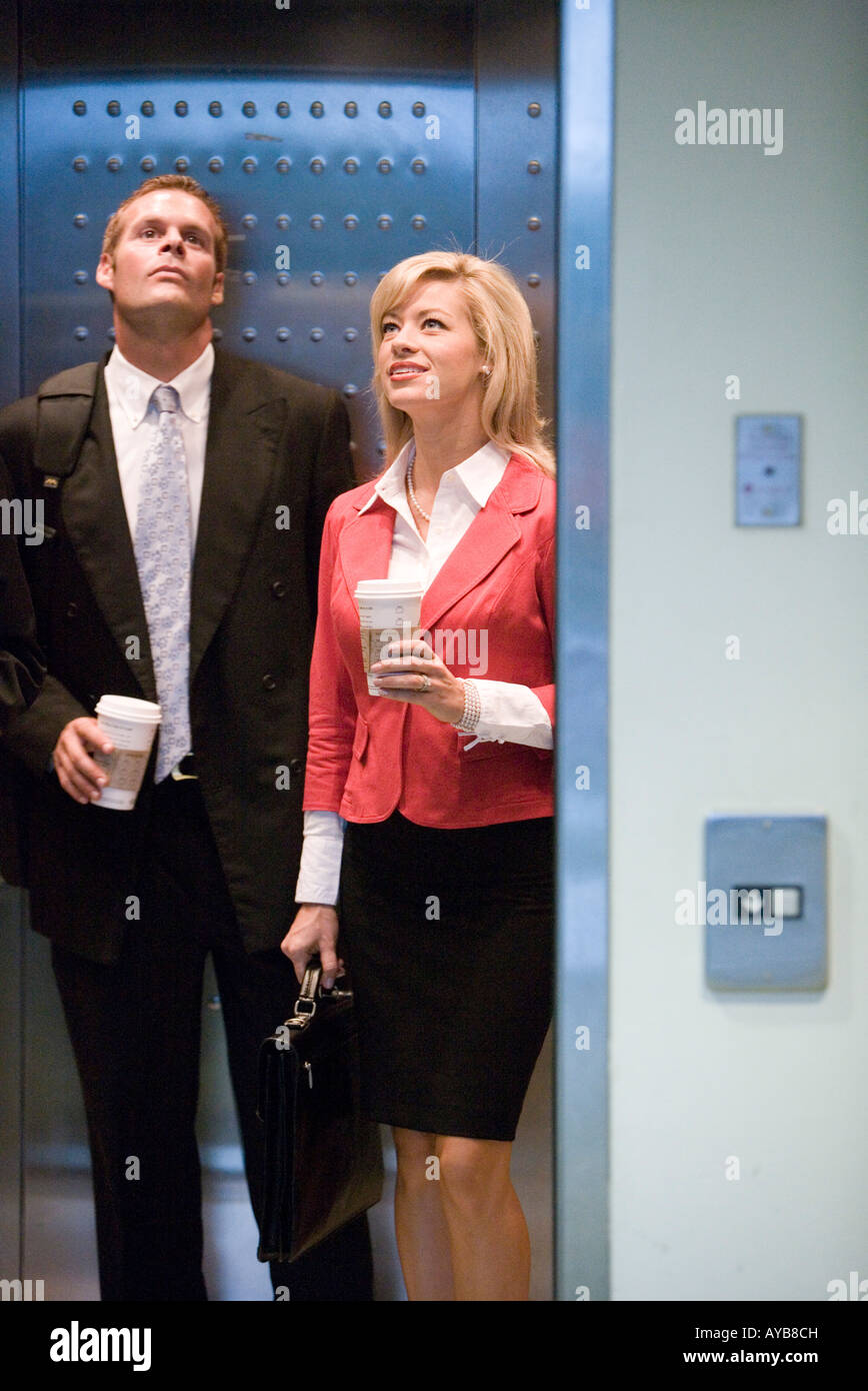 people standing in elevator. business people standing in elevator holding coffee cups waiting for the door to close