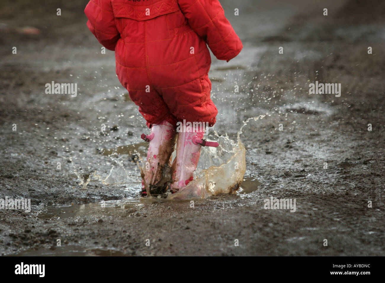 A Child In Red Suit And Pink Wellies Splashes In A Puddle