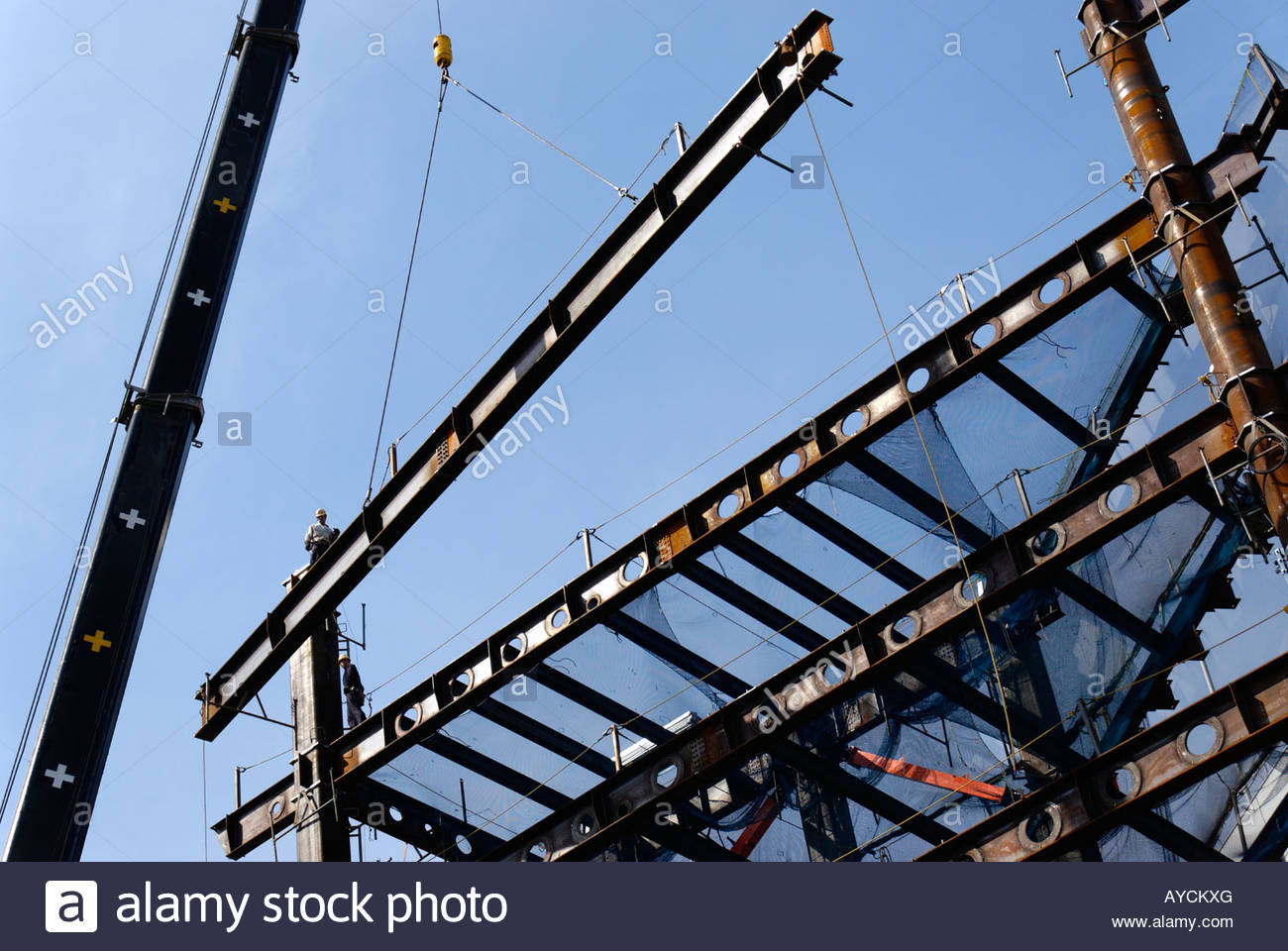 Steel Lifting : Crane lifting steel beam onto a construction site stock