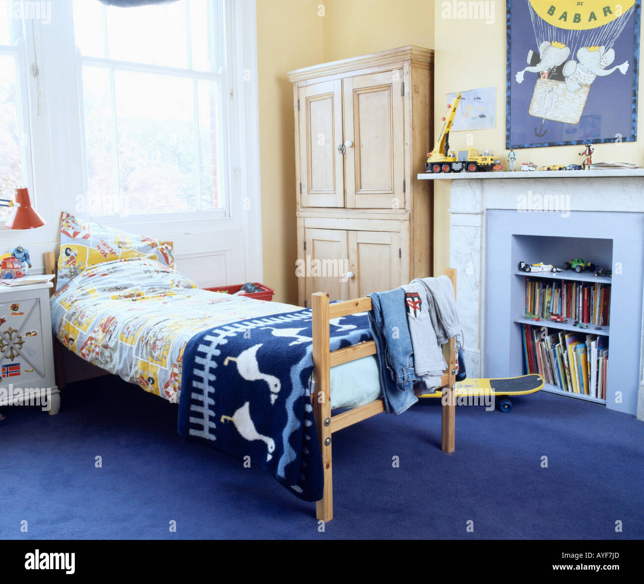 Children's bedroom with blue rug on bed and blue carpet with integral  shelves in fireplace