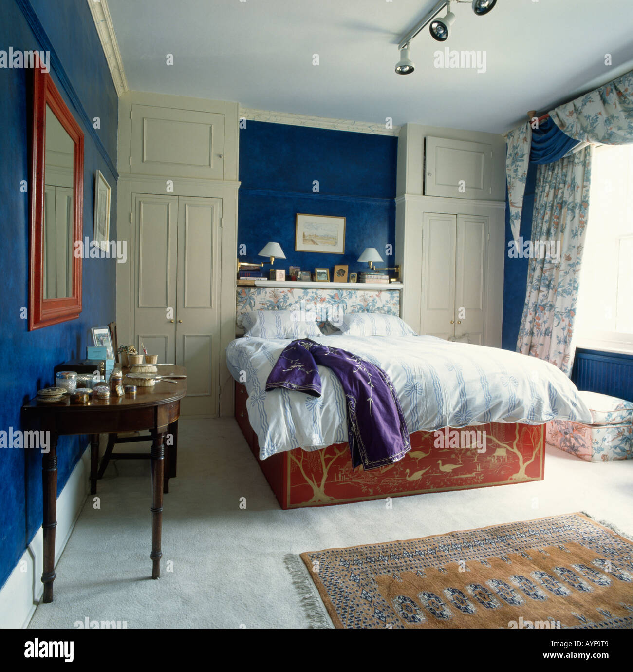 Blue bedroom with grey carpet and wall cupboards. Blue Bedroom With Grey Carpet And Wall Cupboards Stock Photo