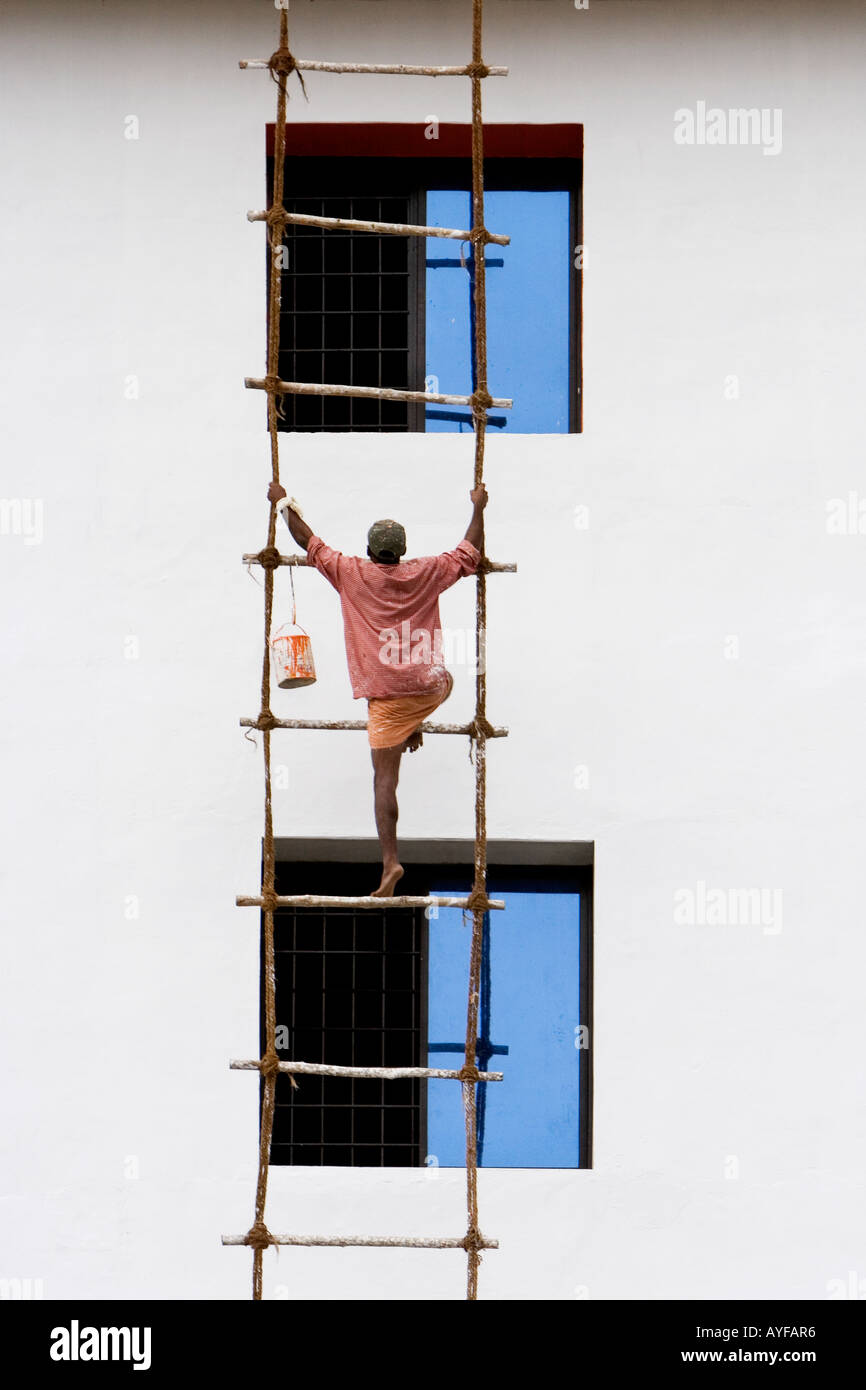 painter climbing up a ladder to work on a wall of a victorian n painter climbing a rope ladder up the side of a building stock photo