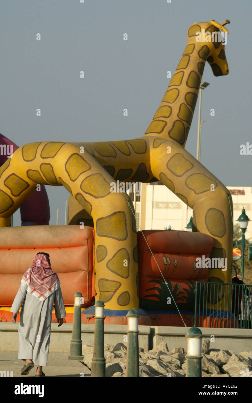 A Kuwaiti Man In A Traditional Thaub Walks Toward A Bouncy Castle Decorated  With A Giant Giraffe Along The Sharq In Kuwait.