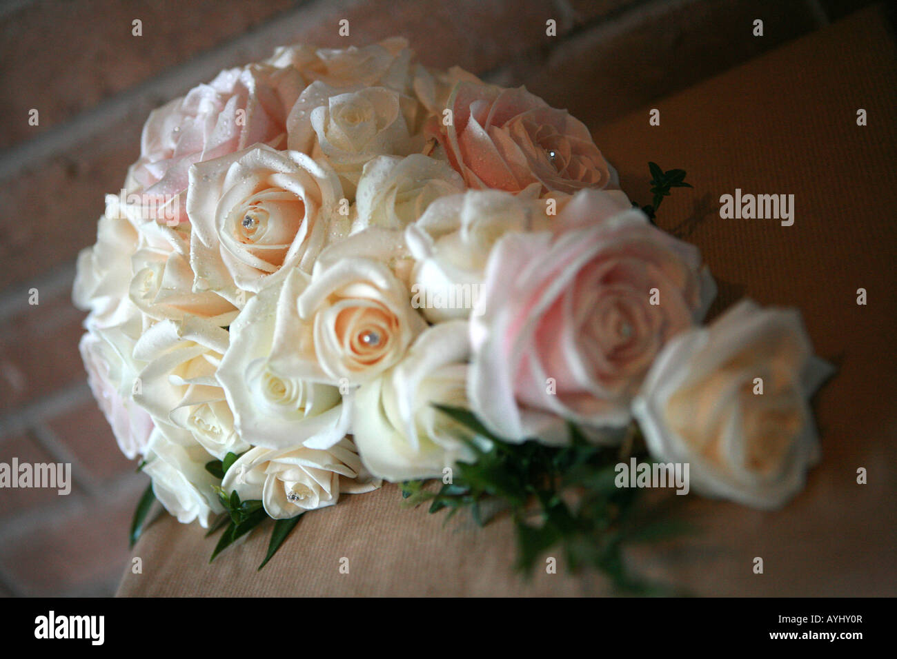 A Bridal Wedding Bouquet Of Soft Pastel Coloured Roses Flowers With Jewel Encrusted Centres Against Brown Red Building Bricks