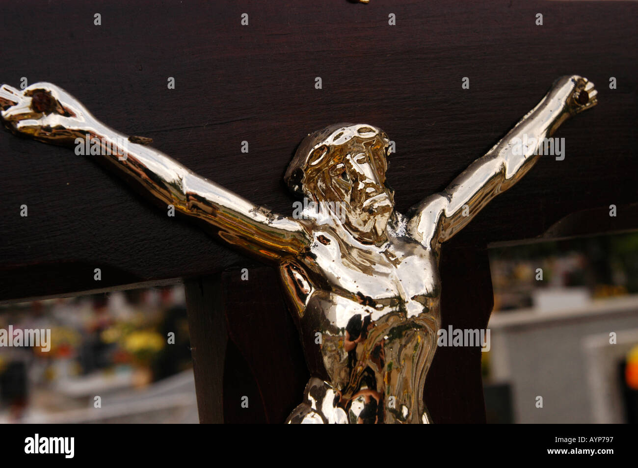 silver metal statue of jesus christ crucified on dark wooden cross