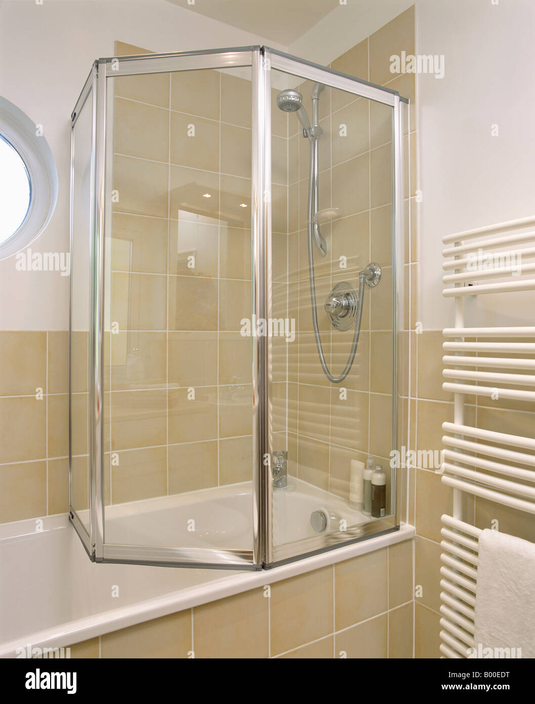 Folding Glass Shower Doors On Bath In Modern Bathroom With Neutral Wall  Tiles