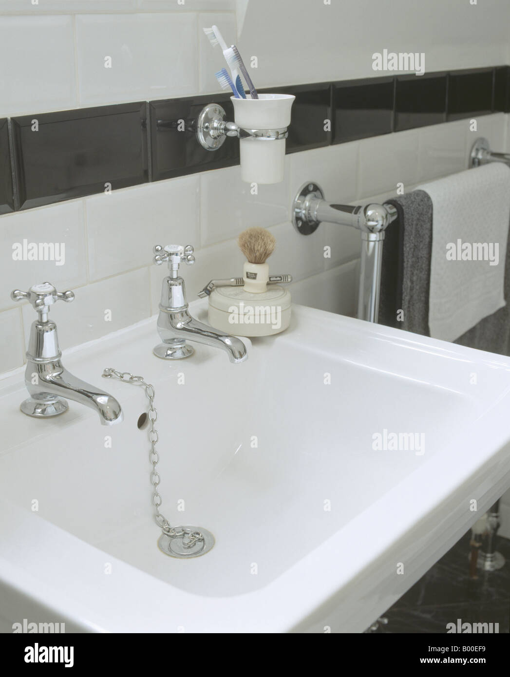 Wall mounted toothbrush holder on black tiled dado above white ...