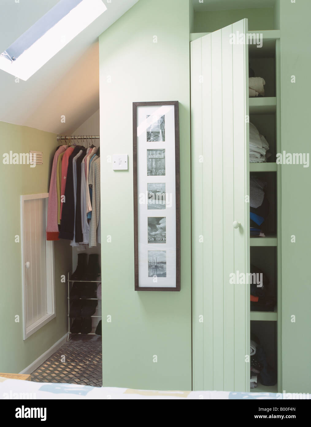 Clothes on hanging rail and cupboard door open on storage shelves ...