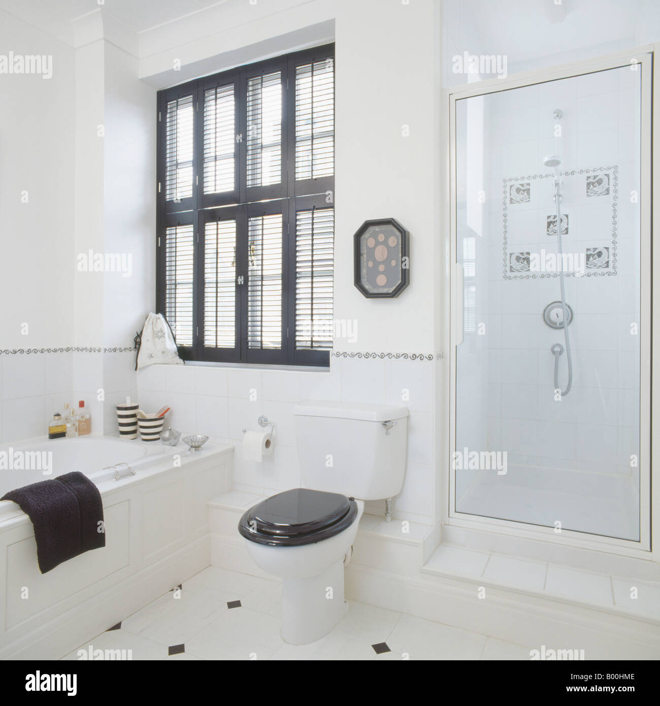 White Toilet With Black Seat. Black plantation shutters above bath and black toilet seat in modern white  bathroom with glass shower door