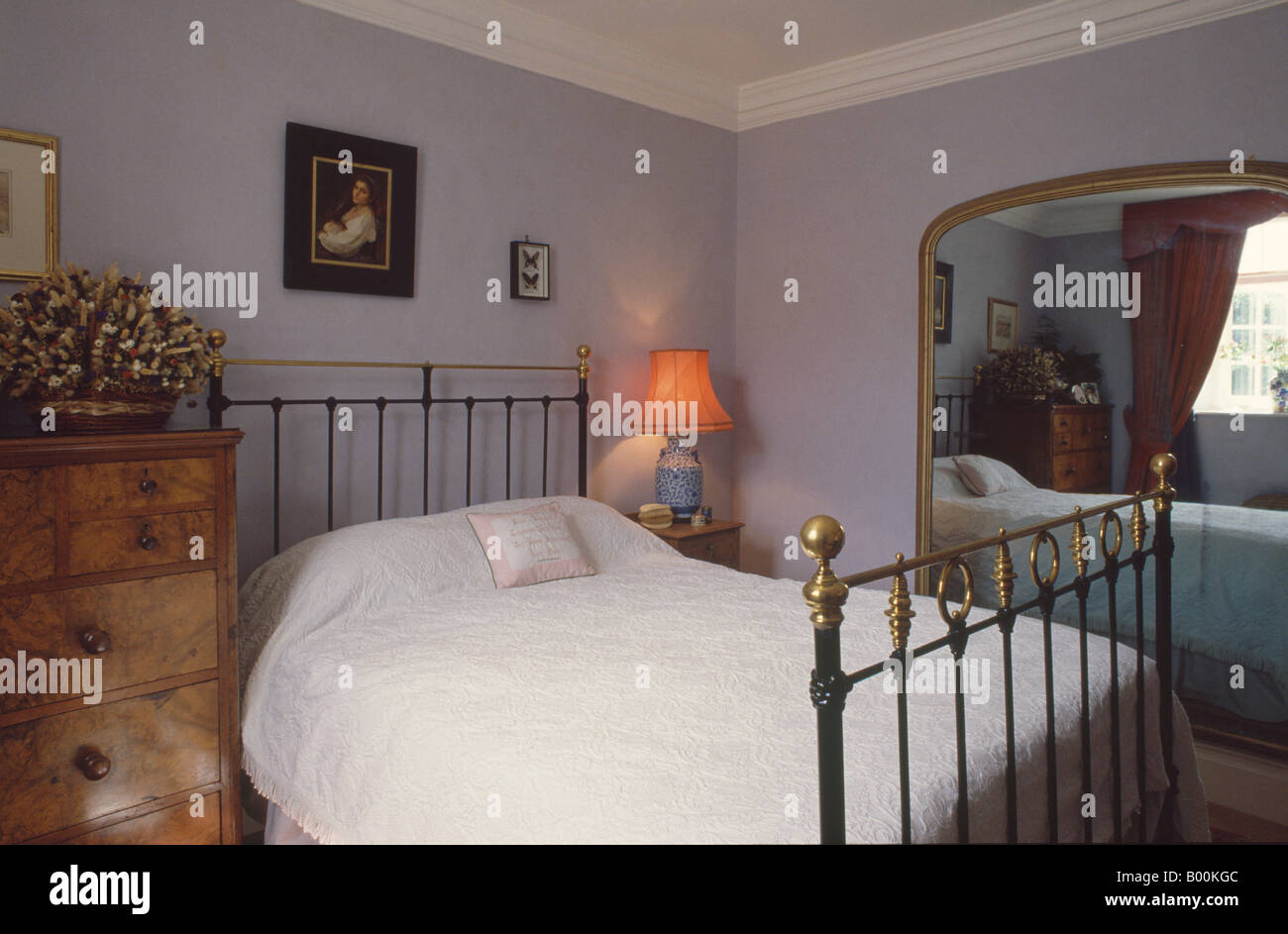 Mirror In The Bedroom Antique Brass Bed And Victorian Gilt Mirror In Mauve Bedroom Stock