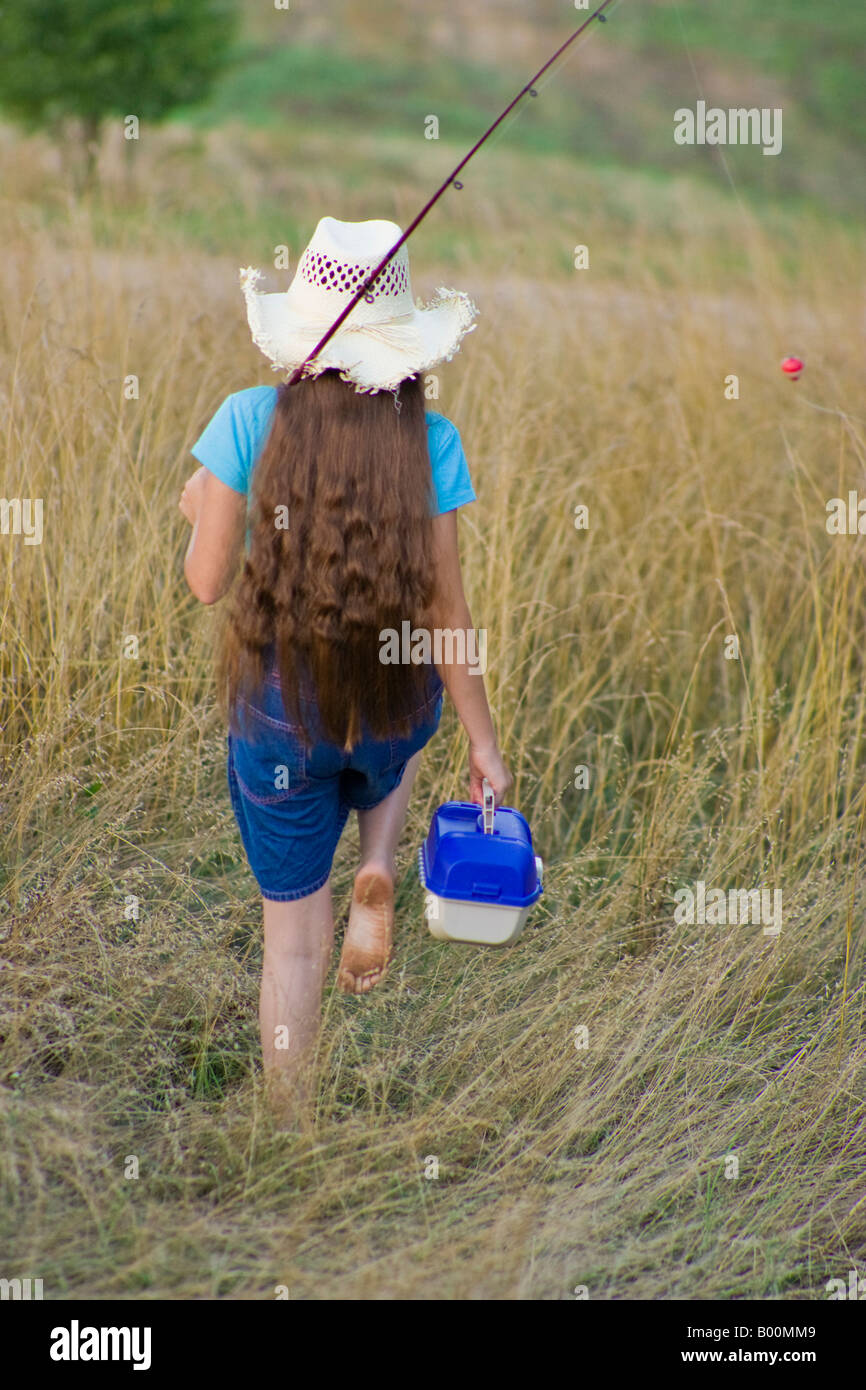 young girl carrying a fishing pole and tackle box stock photo, Fishing Rod