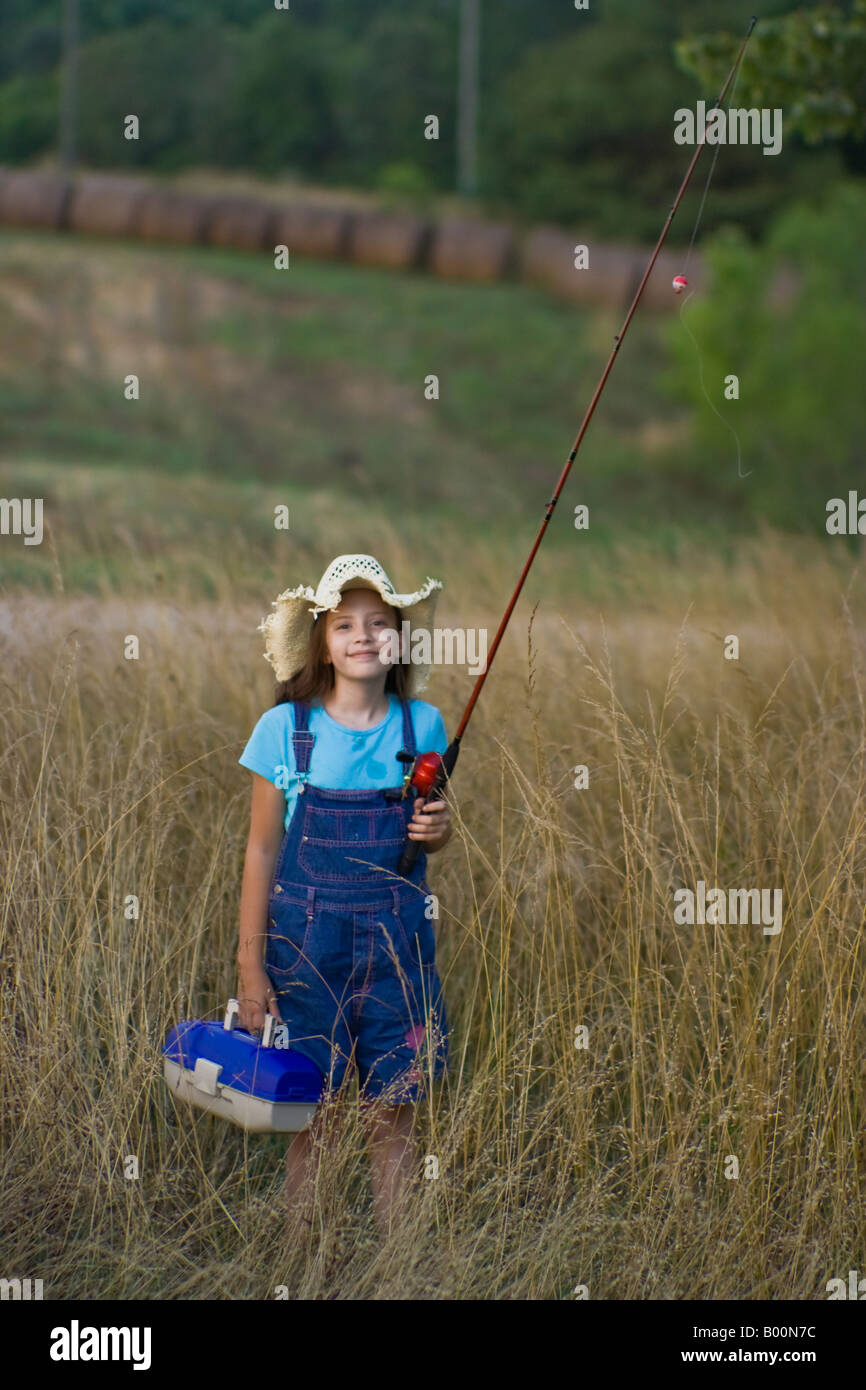 Young girl carrying a fishing pole and tackle box stock for Girl fishing pole