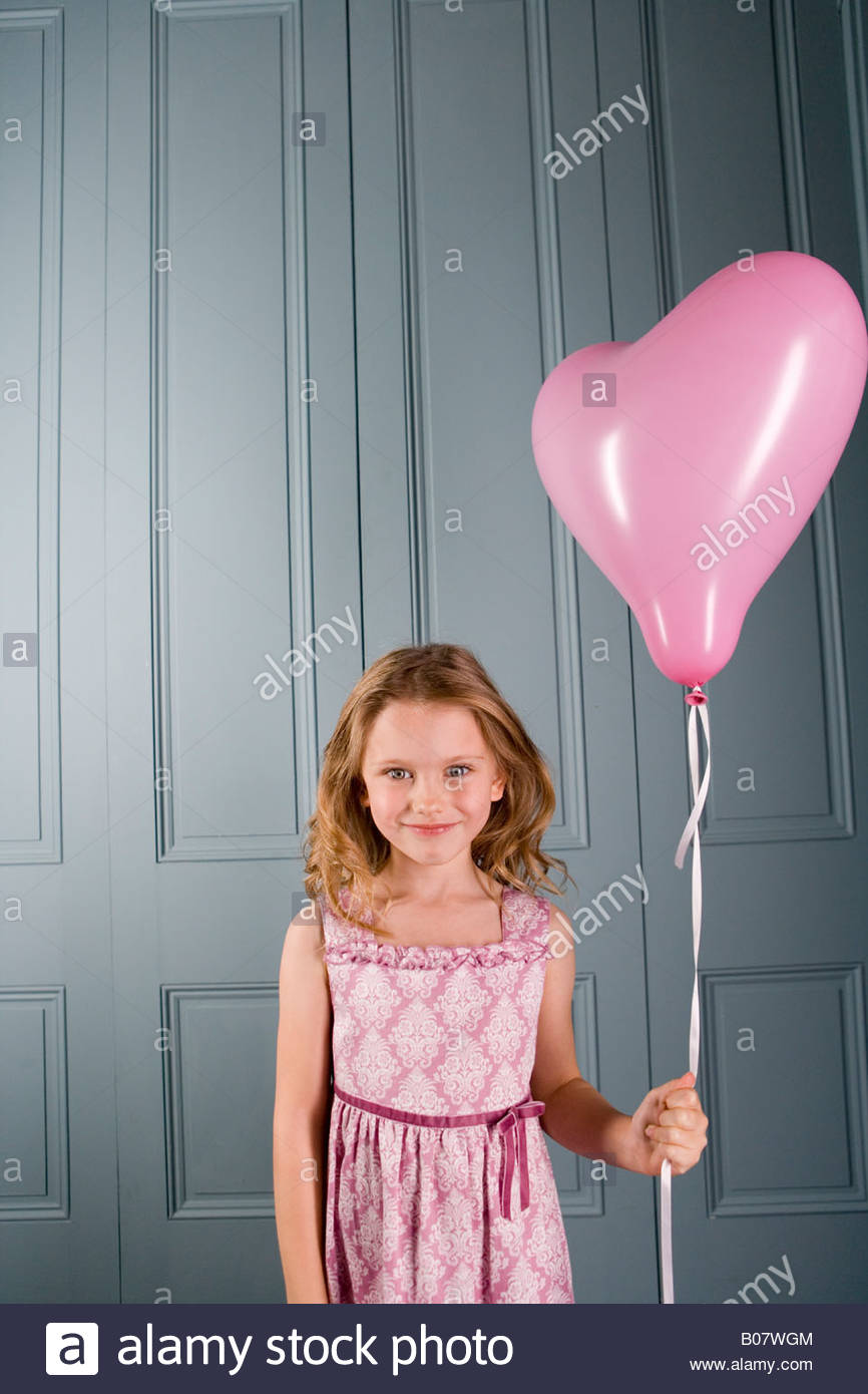little girl in party dress holding pink heart shaped balloon Stock ...