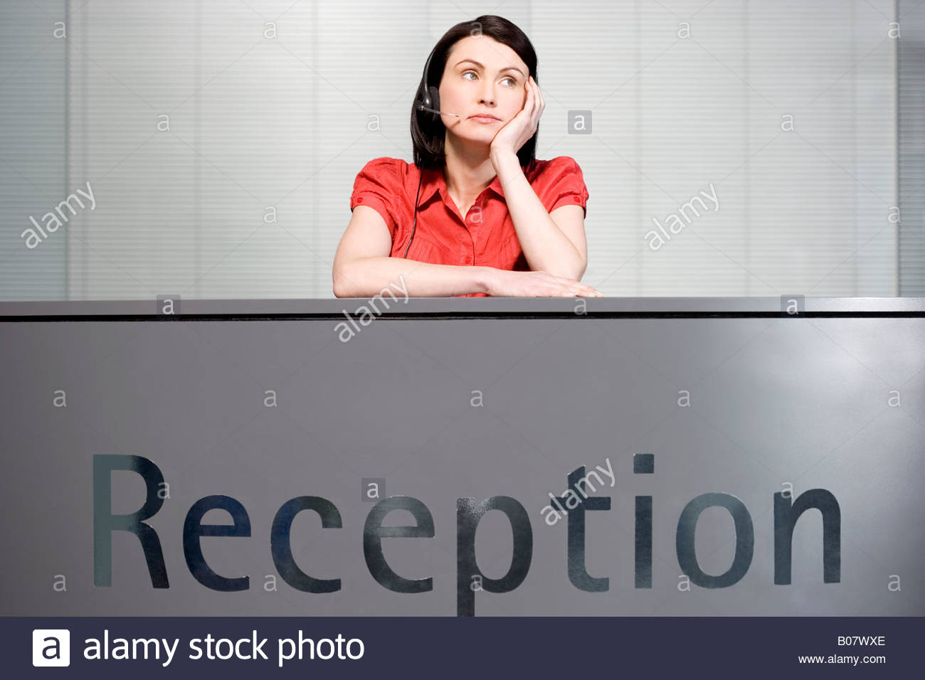 office receptionist in a red blouse looking bored stock photo